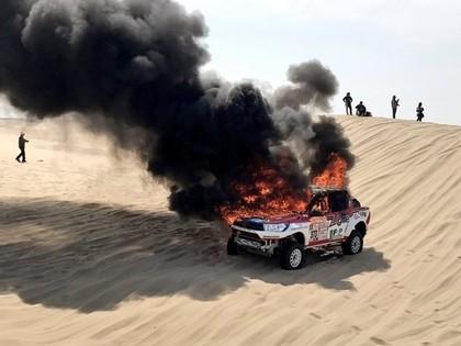 VIDEO: Ekipāža bezspēcīgi noraugās, ka Dakaras rallijā sadeg viņu automašīna